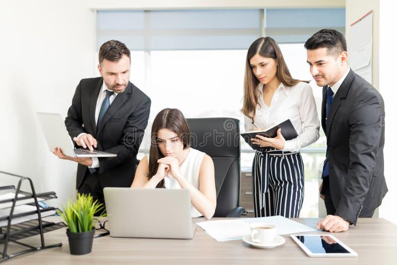 Allvarliga Team Leader And Executives Working på skrivbordet fotografering för bildbyråer