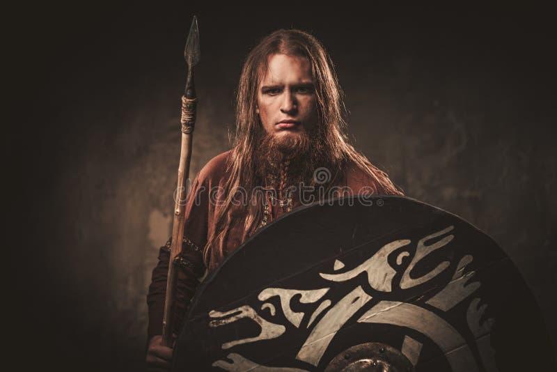 Allvarliga viking med ett spjut i traditionell kläder för en krigare som poserar på en mörk bakgrund royaltyfri foto