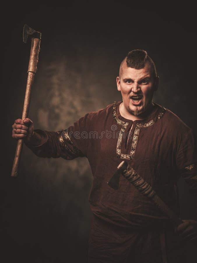 Allvarliga viking med yxa i traditionell kläder för en krigare som poserar på en mörk bakgrund arkivbilder