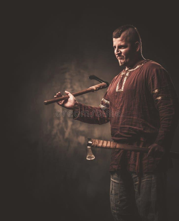 Allvarliga viking med yxor i traditionell kläder för en krigare som poserar på en mörk bakgrund arkivfoto