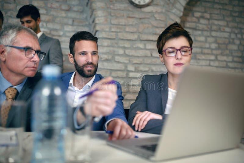 Allvarligt affärsfolk som arbetar på bärbara datorn royaltyfria bilder