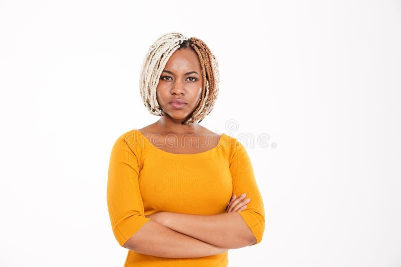 Allvarligt afrikansk amerikankvinnaanseende med korsade armar arkivbilder