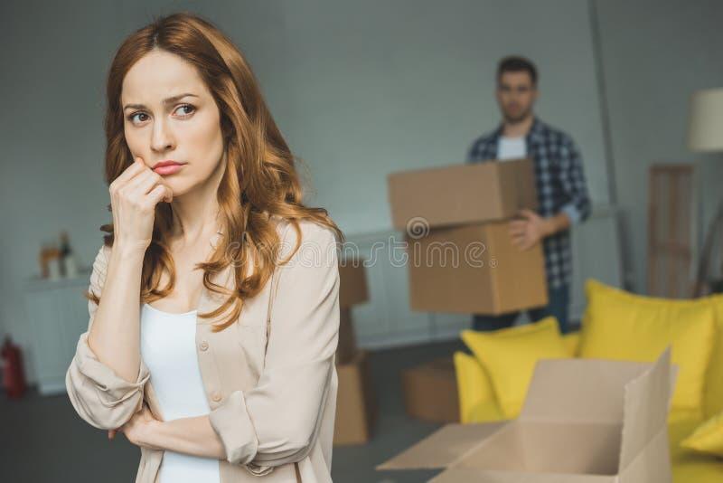allvarligt anseende för ung kvinna med handen på hakan medan make som bakom rymmer kartonger arkivfoto