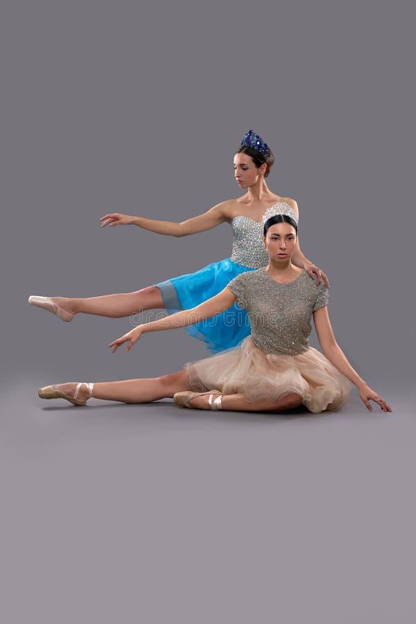 Allvarligt ballerinasammanträde medan kvinnlig partner som bakom poserar royaltyfri fotografi