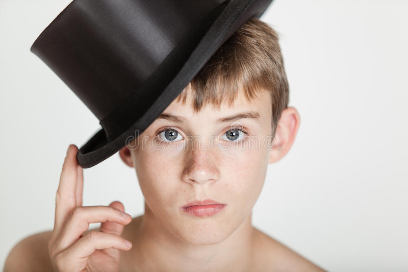 Allvarligt barn som tippar hans hatt på huvudet royaltyfria foton