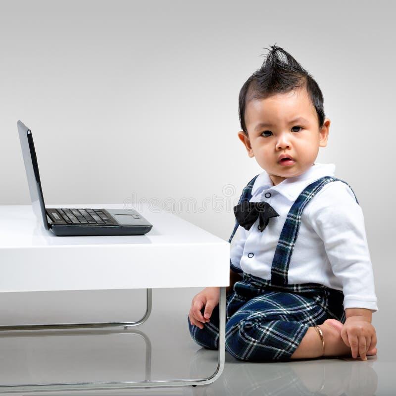Allvarligt behandla som ett barn pojken med bärbara datorn royaltyfri foto