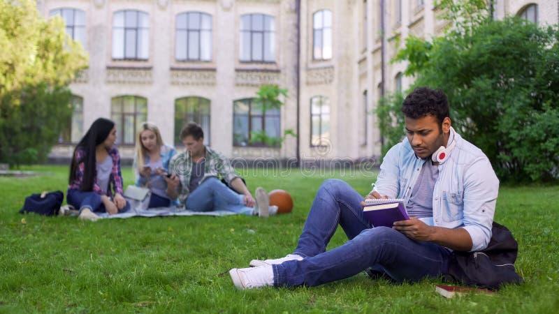 Allvarligt biracial sammanträde för manlig student på gräs- och handstilessäen som gör läxa royaltyfri fotografi