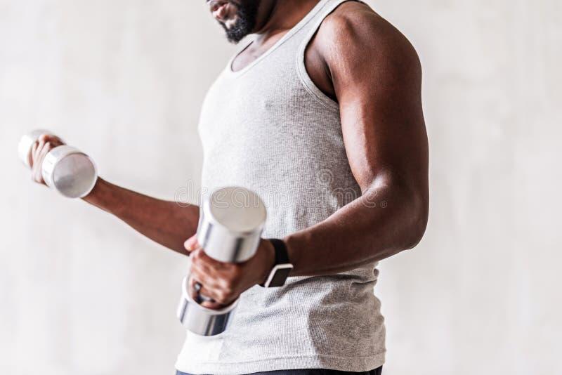 Allvarligt brunn-byggande afrikansk idrottsman nen med skägget som utför genomkörare med handvikter royaltyfri bild