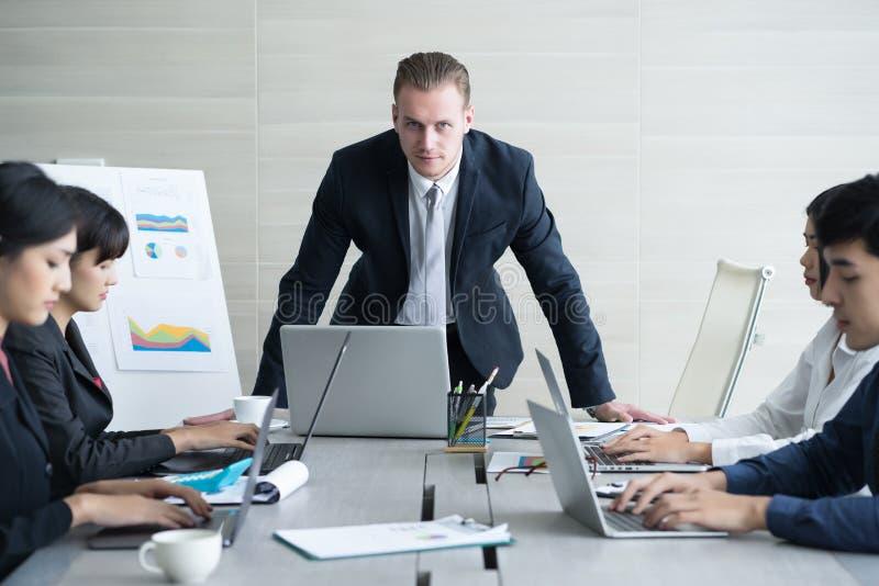 Allvarligt framstickande som diskuterar arbete med hans kollegor varm diskussion royaltyfri bild