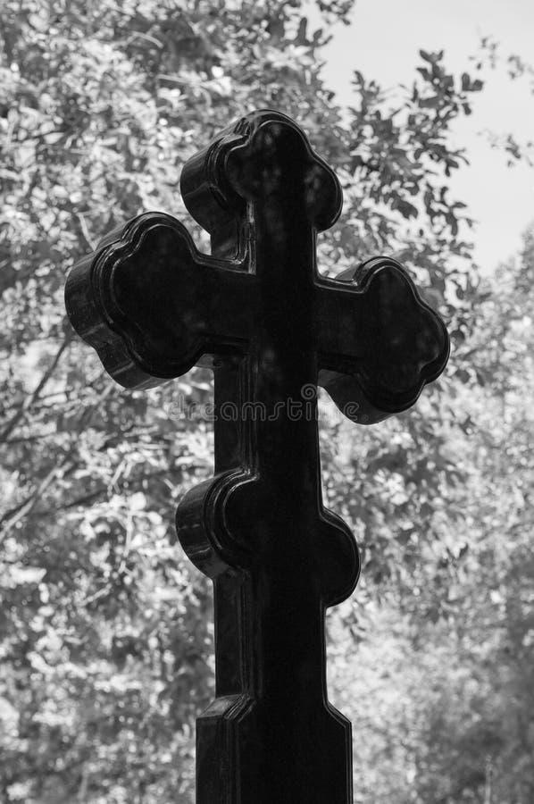 Allvarligt kors av svart granit på bakgrunden av lövverk av träd Begreppet av död, religion, tro Svartvit bild arkivfoton