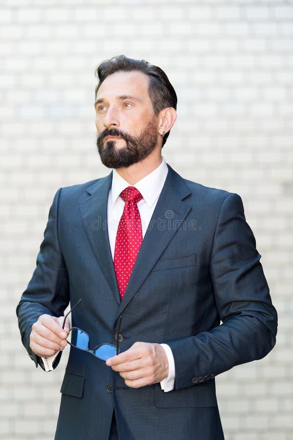 Allvarligt mananseende med hans exponeringsglas mot den vitt bakgrunden och tänka royaltyfri fotografi