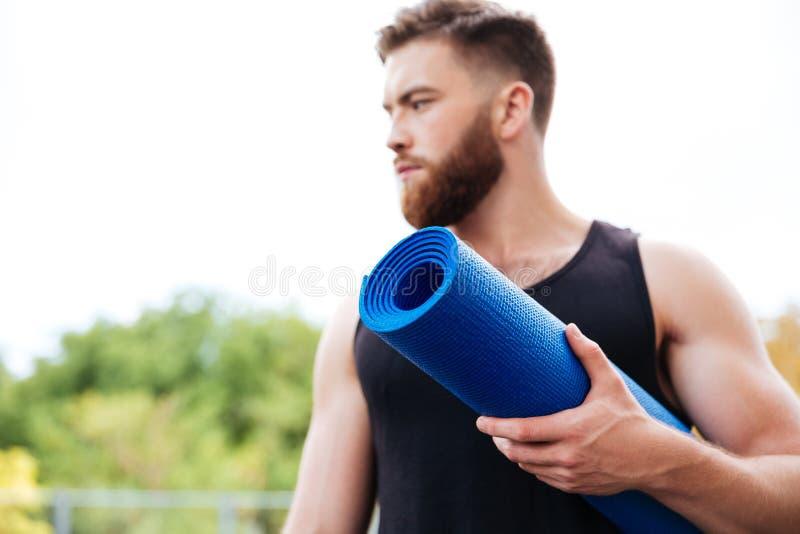 Allvarligt manligt yogainstruktörinnehav som är mattt och utomhus ser bort royaltyfria bilder