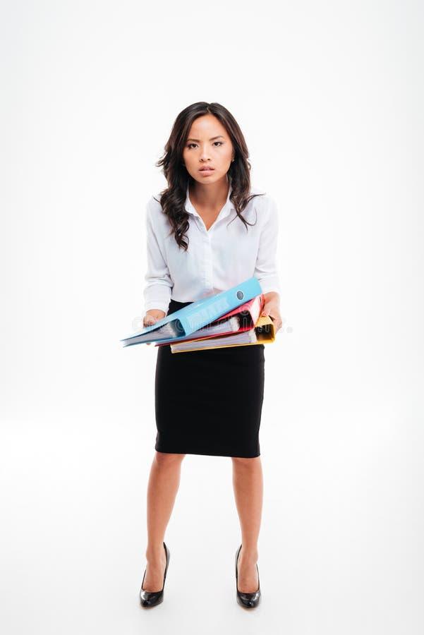 Allvarligt smart ungt asiatiskt affärskvinnaanseende och färgrika mappar för visning royaltyfri fotografi