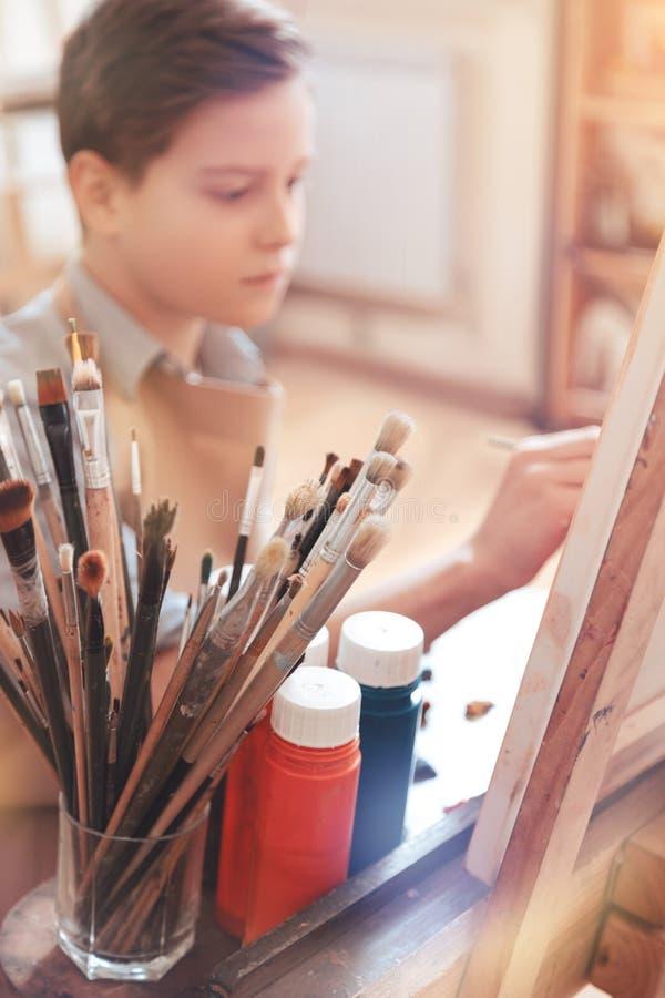 Allvarligt tonårigt pojkemålningmästerverk i studio fotografering för bildbyråer