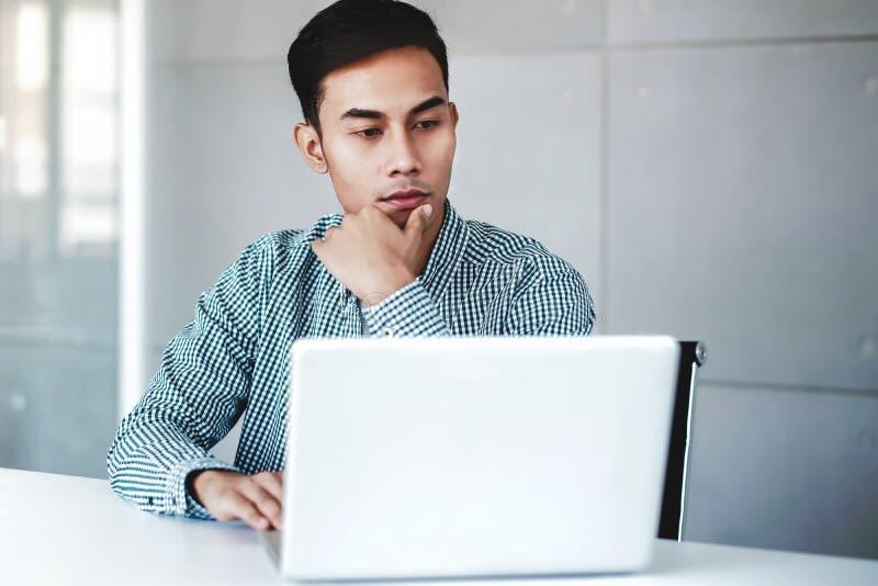 Allvarligt ung affärsman Working på datorbärbara datorn i regeringsställning Hand på skenbenet som sitter på skrivbordet med fund royaltyfri foto