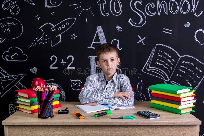 Allvarligt utmärkt skolpojkesammanträde på skrivbordet med böcker, skolatillförsel, med båda armar som lutas en till andra royaltyfria foton