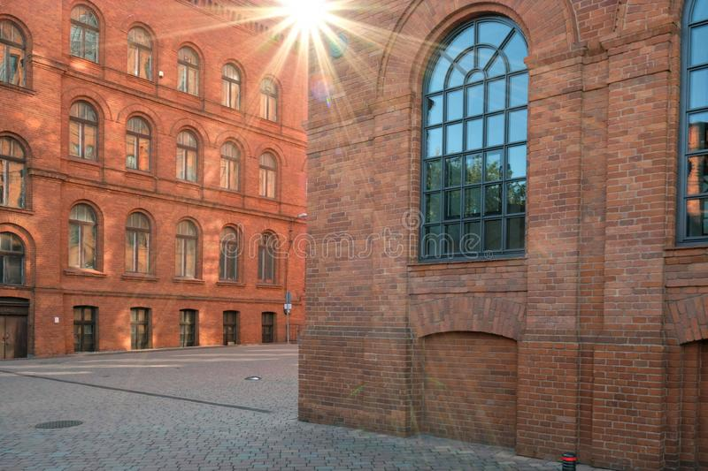 Allyeway with red brick industrial buildings with sun flare background.  stock photos