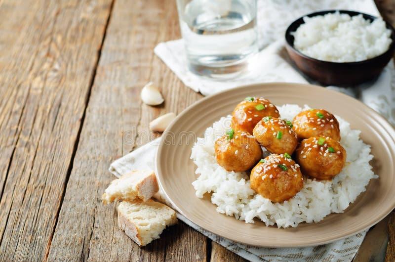 Almôndegas alaranjadas cozidas da galinha com arroz foto de stock