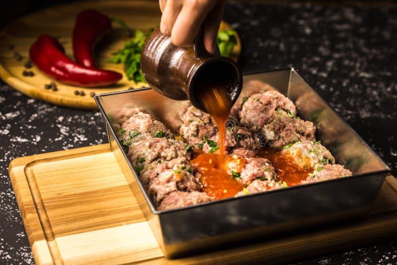 Almôndegas cruas da carne de porco no prato de cozimento metálico no molho de tomate imagem de stock