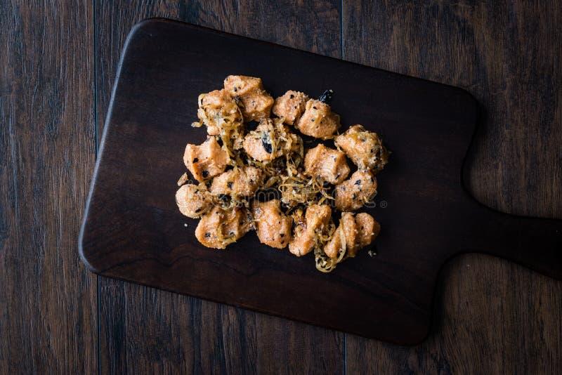 Almôndegas turcas do Bulgur de Sikma Kofte com cebolas caramelizadas/Fellah Bulghur Kofta na placa de madeira fotos de stock