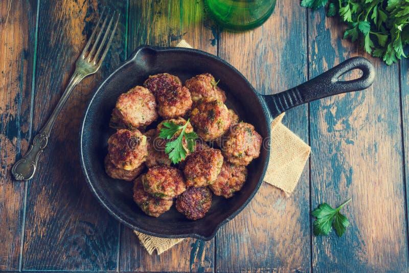 Almôndegas roasted caseiros da carne no frigideira do ferro fundido na tabela de madeira na cozinha, salsa fresca, forquilha do v imagens de stock