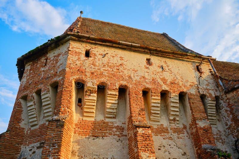 Alma Vii Fortified Church, com luz solar quente Destino turístico popular na Transilvânia, Romênia foto de stock