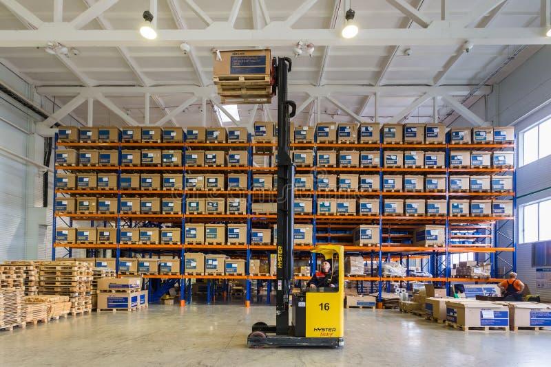 Almacén moderno grande de LADA-IMAGE con las carretillas elevadoras para los recambios del vehículo del almacenamiento foto de archivo