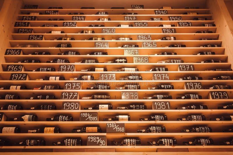 Almacenamiento con las botellas de vino de Oporto por año, bebidas del vintage en estante de una tienda en venta fotografía de archivo