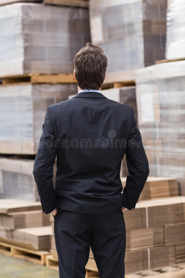 Almacene al encargado en el traje que se coloca con las manos en bolsillos foto de archivo
