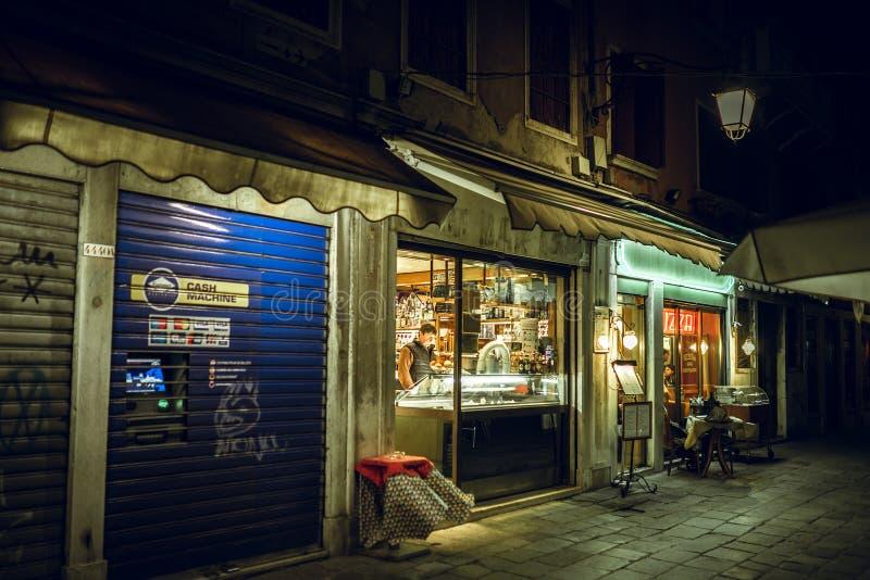 Almacene el vidrio de la ventana por noche, Venecia, Italia foto de archivo