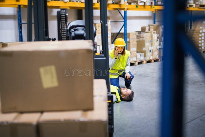Almacene a los trabajadores después de un accidente en un almacén fotos de archivo libres de regalías