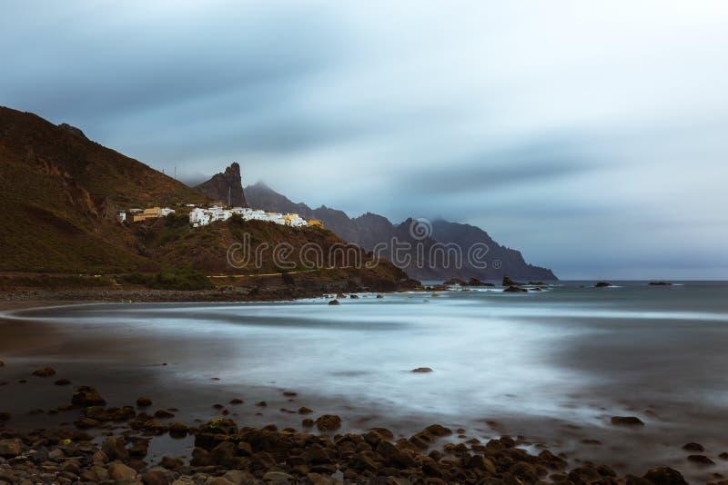 Almacigadorp op rotsachtige kustlijn tijdens stormachtig weer stock foto