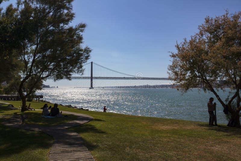 Almada, Portogallo: CIRCA maggio 2019: La gente che si rilassa al parco della riva del fiume un giorno soleggiato fotografie stock libere da diritti