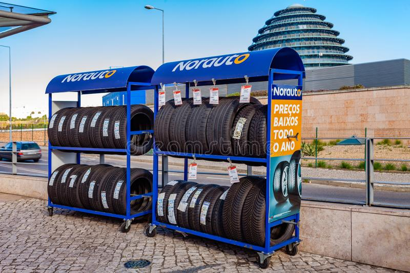 Almada, Portugal - October 24, 2019: Tires on rack at Norauto car or auto parts shop and service station or auto repair shop in. Almada Forum shopping mall or stock photography