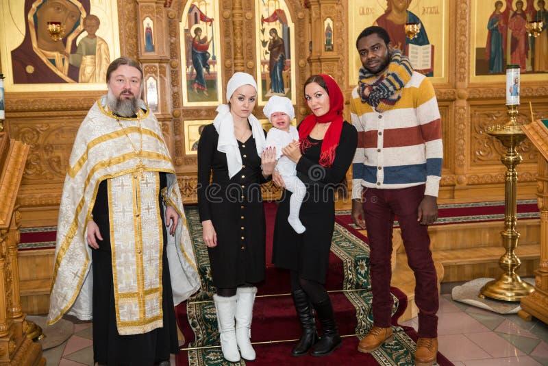 ALMATY KASAKHSTAN - DECEMBER 17: Dopceremoni på December 17, 2013 i Almaty, Kasakhstan. Familj som firar dop in royaltyfri bild