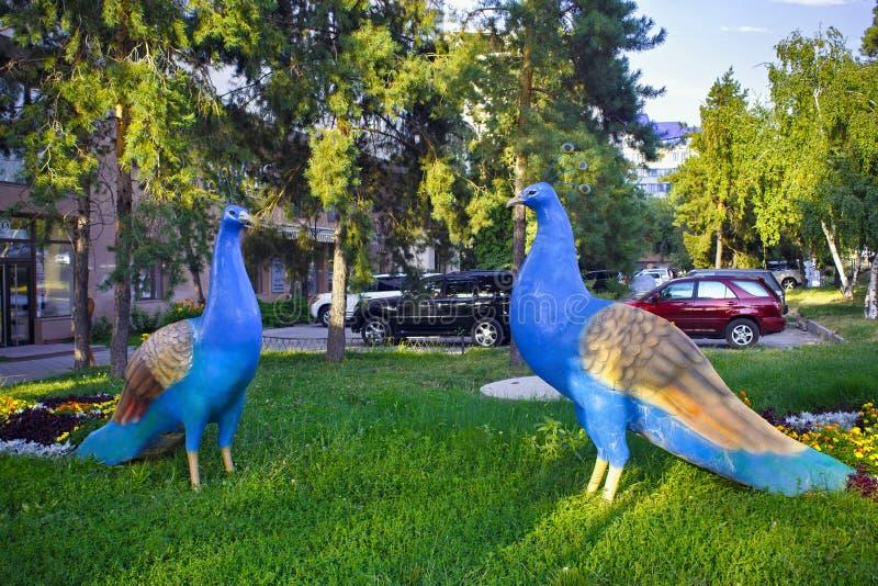 ALMATY KASAKHSTAN - JULI 27, 2017: Stadsskulptur av blåa påfåglar i mitten av Almaty arkivfoton