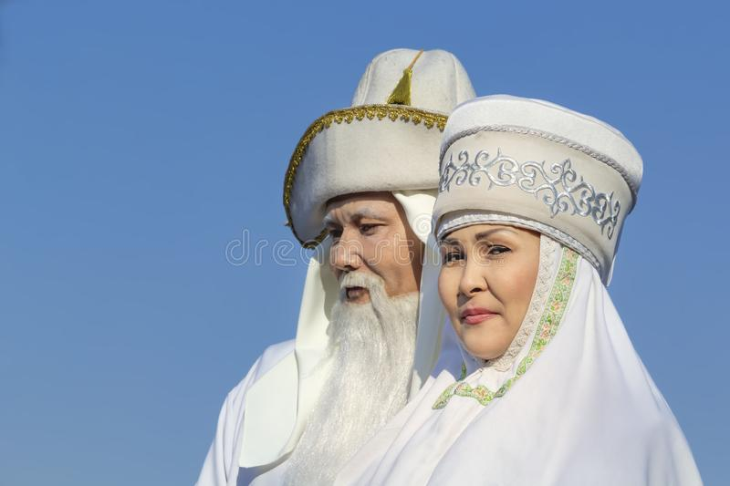 Elderly men and women in white national Kazakh clothes against the background of the sky during the carnival holiday. Almaty, Kazakhstan - March 21, 2019 royalty free stock photo