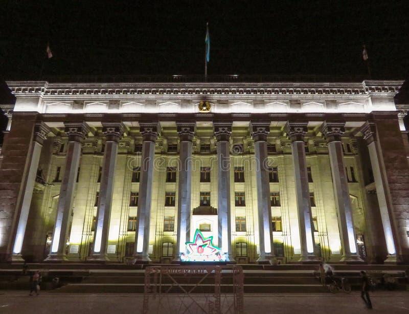Almaty - opinião da noite à casa velha do quadrado e do governo fotografia de stock