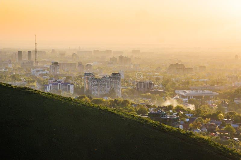 Almaty stad i dimman i solnedgång med smog och damm i luften, fotografering för bildbyråer