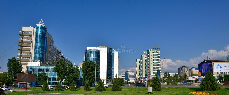 Almaty stadsbyggnader på sommardag med blommor och fontain framme arkivbilder