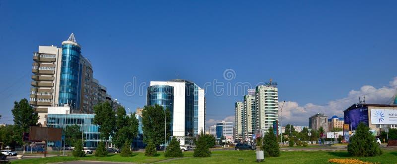 Almaty-Stadtgebäude am Sommertag mit Blumen und am fontain in der Front stockbilder