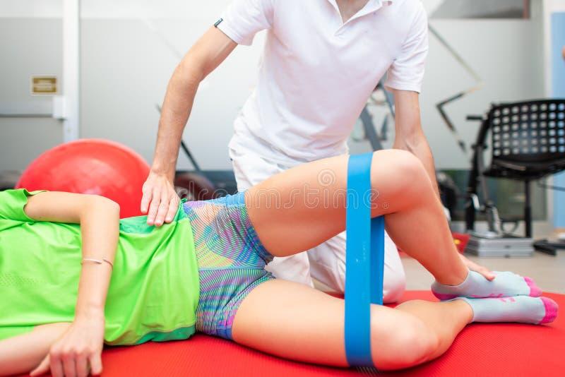 almeja Ejercicio para los músculos adicional-rotativos de la cadera Fisioterapeuta hacia un atleta fotos de archivo