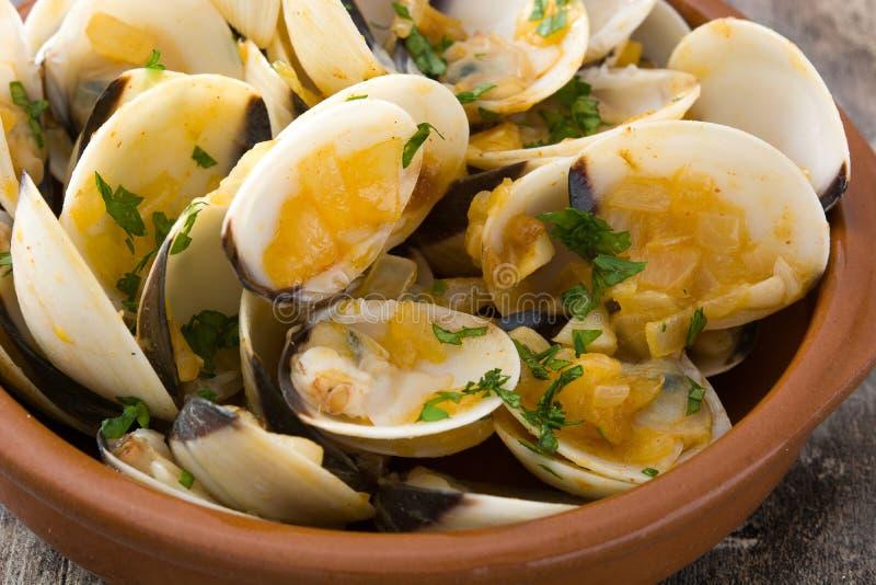 Almejas con la salsa del marinera Almejas un marinera del la Receta española en la madera fotografía de archivo