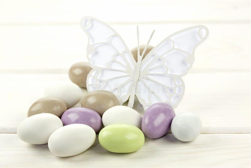 Almendras azucaradas coloreadas y mariposa parecida al papel imagen de archivo