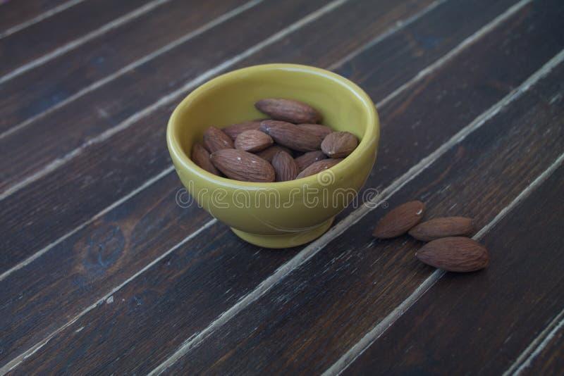 Almendras dulces en un cuenco amarillo en la madera imagenes de archivo