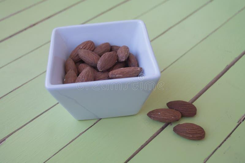 Almendras dulces en un cuenco blanco en la madera verde foto de archivo