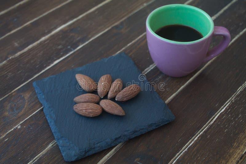 Almendras dulces en una placa y un café de la pizarra en la madera imagen de archivo
