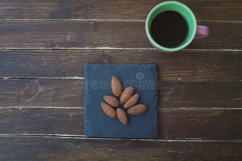 Almendras dulces en una placa y un café de la pizarra en la madera desde arriba fotografía de archivo