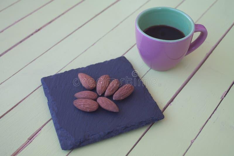 Almendras dulces en una placa y un café de la pizarra en la madera verde imagen de archivo libre de regalías