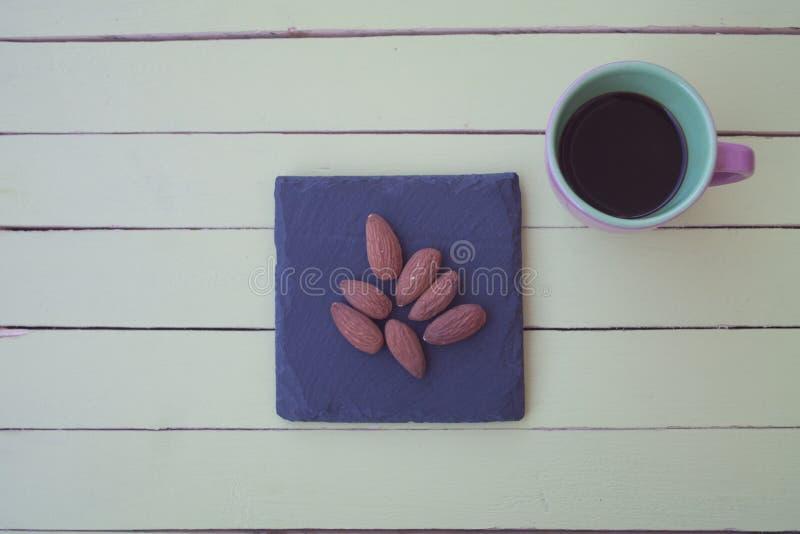 Almendras dulces en una placa y un café de la pizarra en la madera verde desde arriba imágenes de archivo libres de regalías